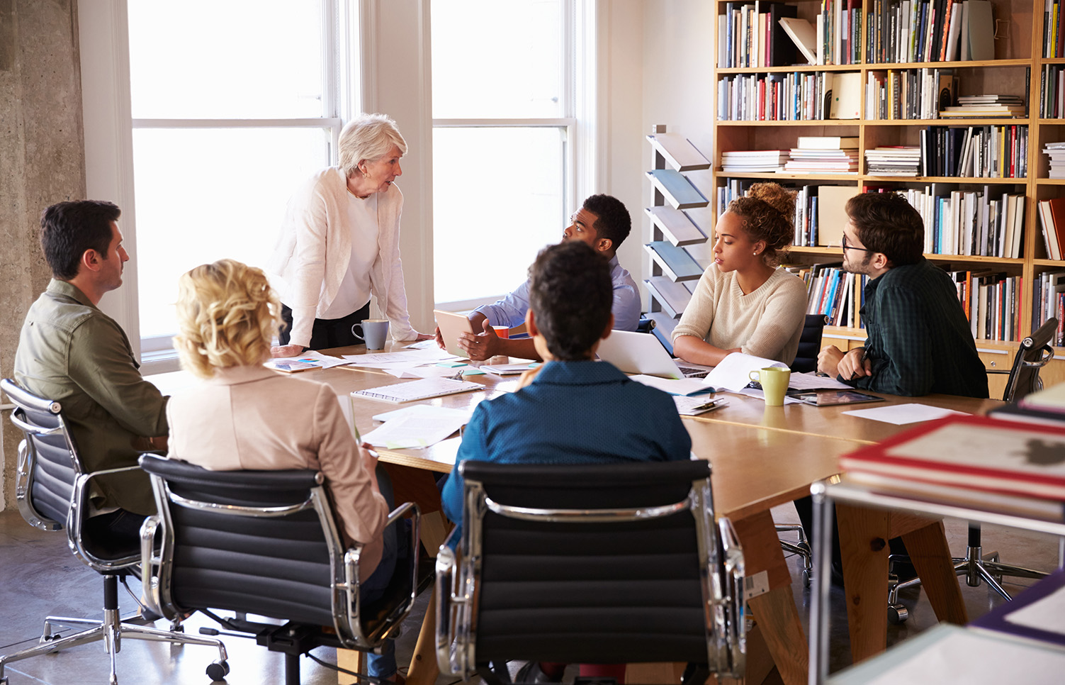 Senior Businesswoman Addressing Team Meeting Around Table