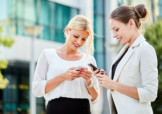 Two business woman standing at the street and using mobile phone