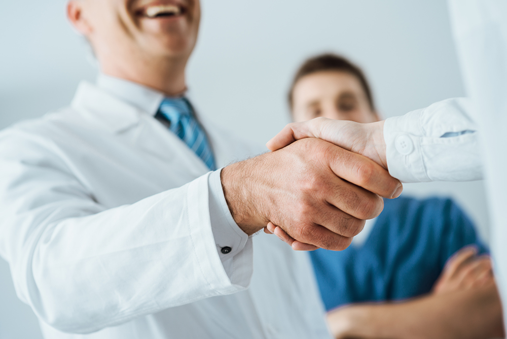 Professional doctors handshaking at hospital, hands close up, agreement and hiring concept
